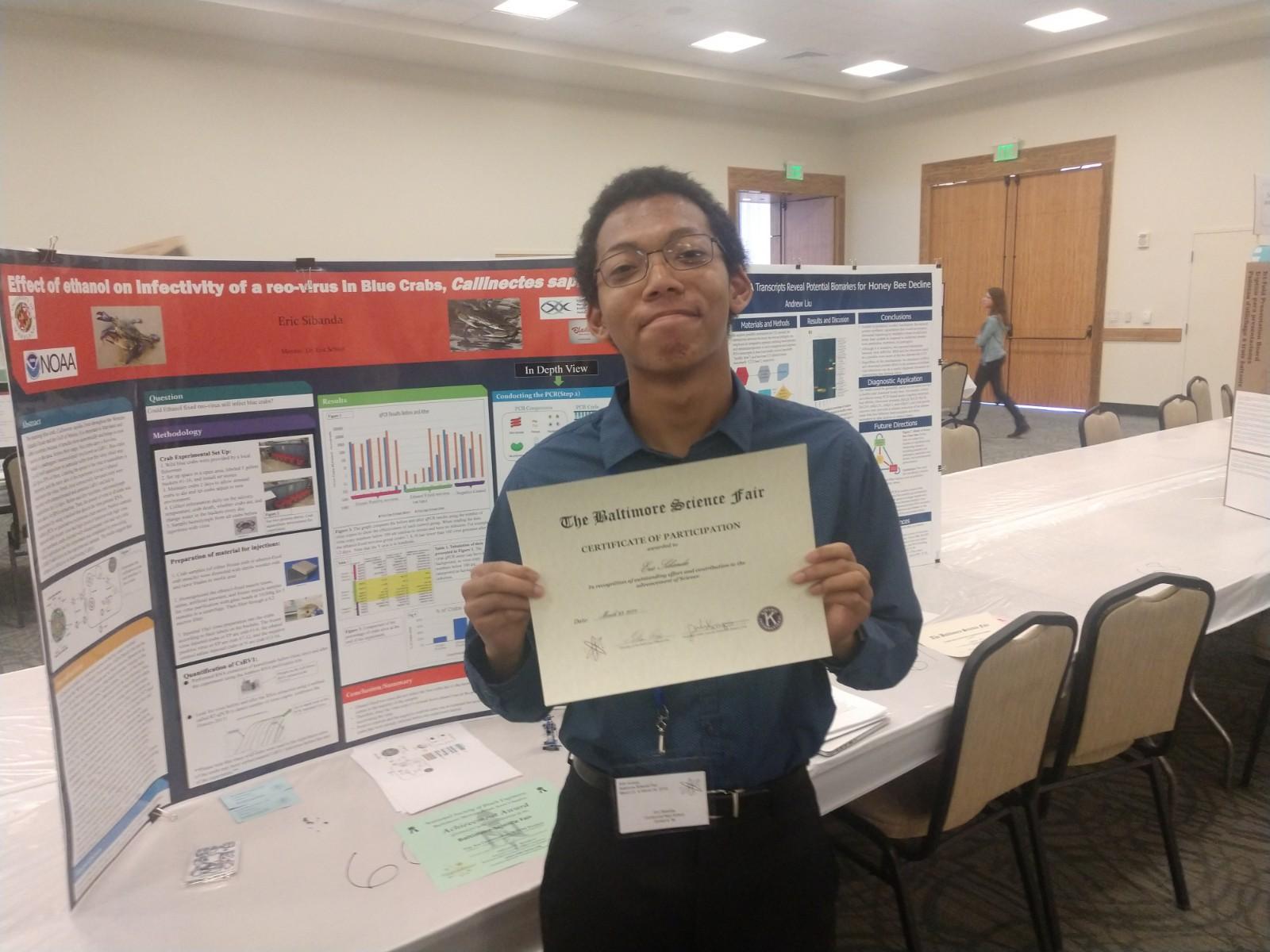 Eric Sibanda holds up science fair certificate