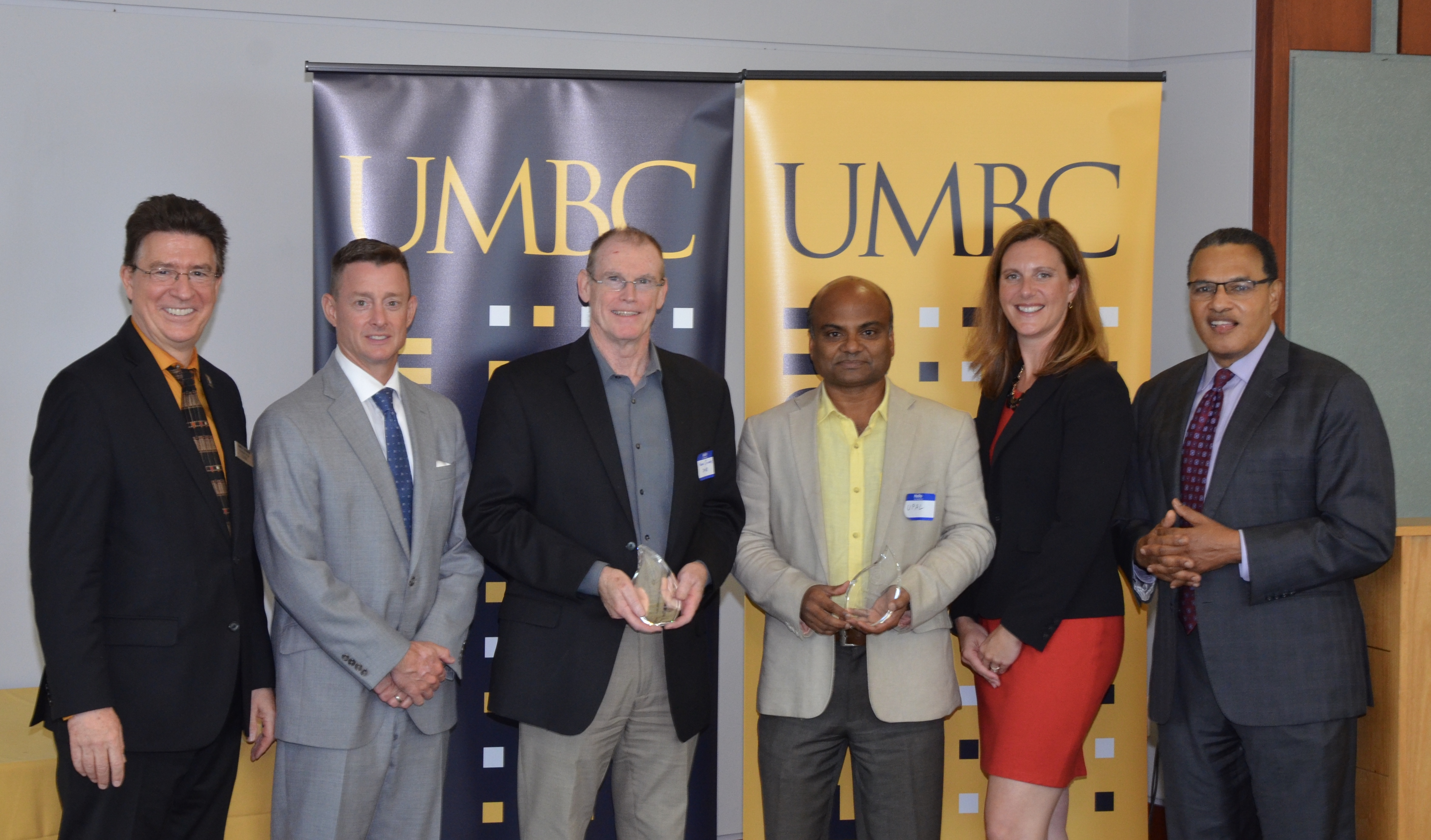 Upal Ghosh and Kevin Sowers stand in front of UMBC banners with UMBC officials