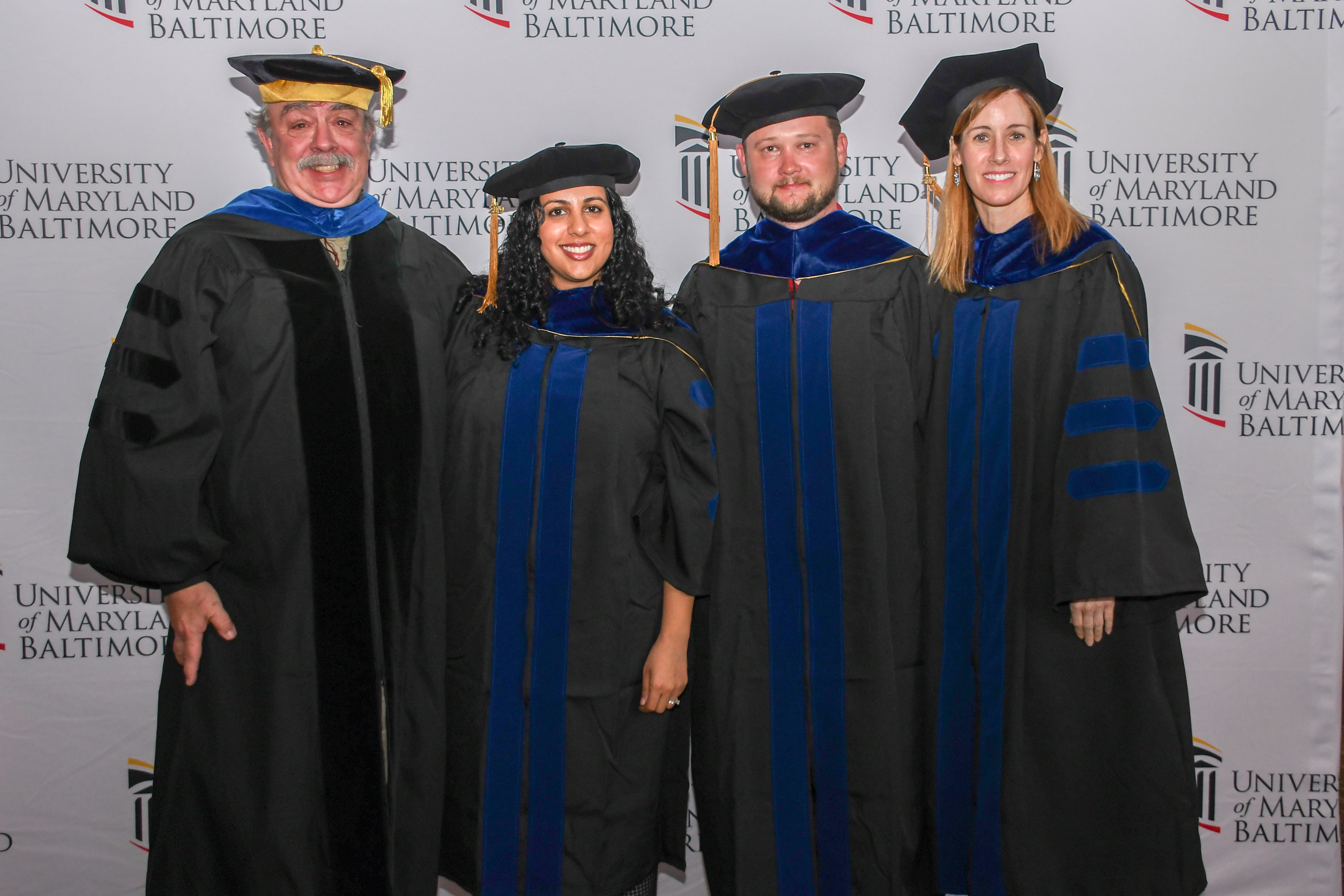Al Place, Saddef Haq, Ben Oyler, and Mary Larkin in graduation robes and regalia
