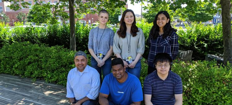 6 members of the Chatterjee Lab standing outside among trees