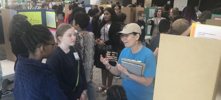 IMET scientist speaks with students at a science fair