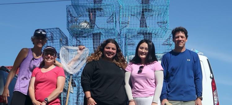 Olivia, Mingli, and Eric in front of cages