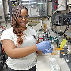 Jeanette Davis in a lab with a NOAA t-shirt