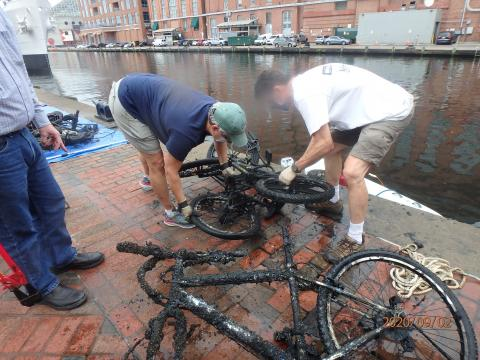 two people inspect two bicycles that were just pulled out of the water