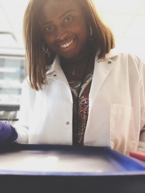Adjele Wilson in a lab coat in a lab