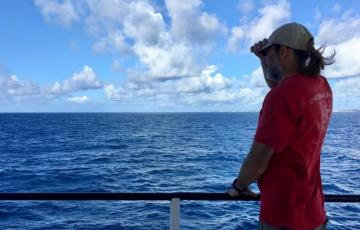 Michael Gonsior stands at the rail of the ship looking at the horizon