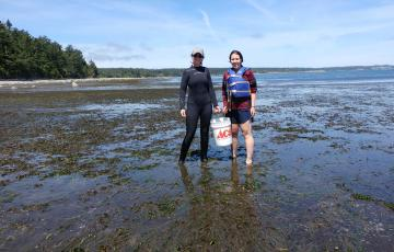 Tori and a labmate hold a bucket in a mud flat