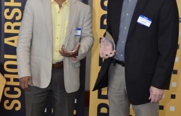 Kevin Sowers and Upal Ghosh hold clear glass trophies