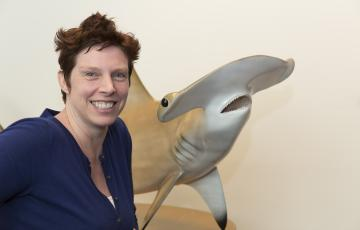 Dr. Dooley poses with her hammerhead shark statue named Belle