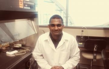 Muddassar Iqbal in a lab coat next to a fume hood
