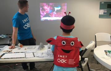 child wearing a crab headband playing a video game
