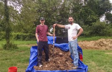 Ryan Powell and colleague standing in front of a dirt pile with a shovel
