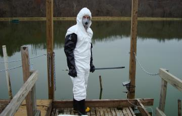 Kevin Sowers wearing PPE in front of water at a contaminated site