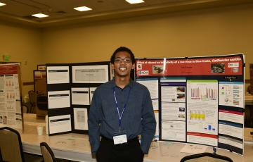 Eric Sibanda stands in front of a research poster