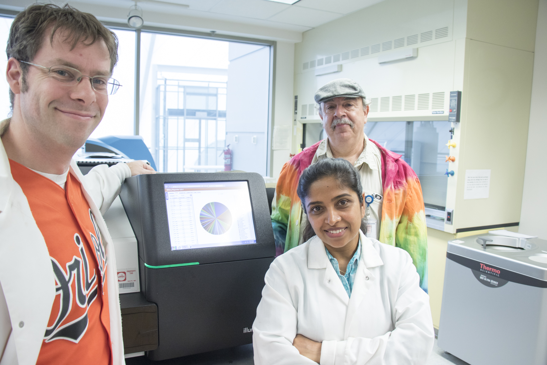 Sabeena Nazar stands next to machine in BAS Lab with Allen Place and Ernest Williams