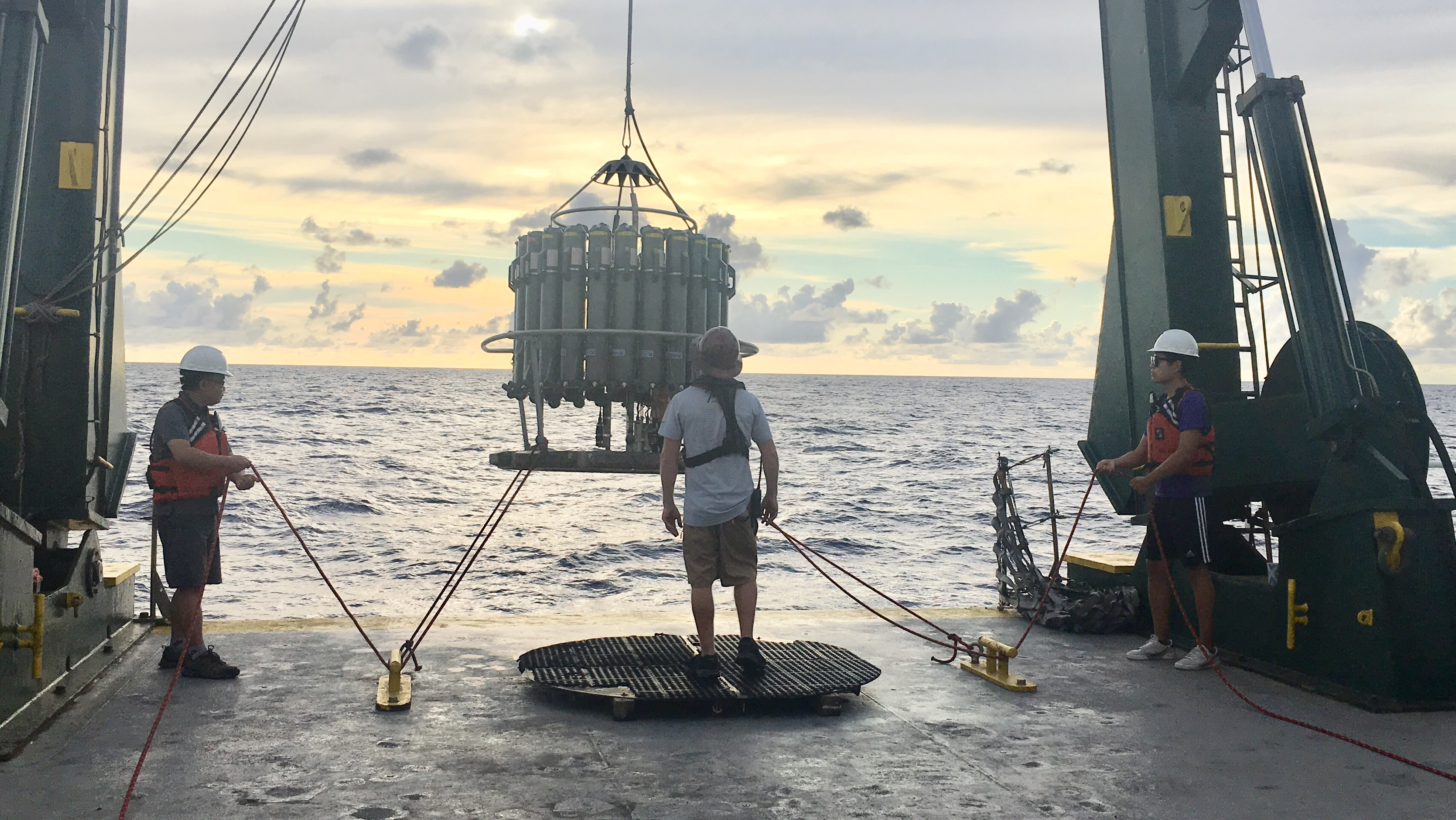 a team of scientists lowers a CTD into the water off of a research boat